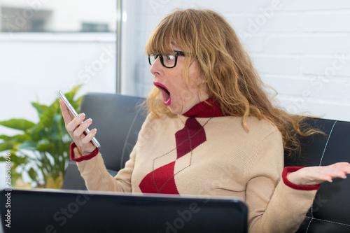Leinwandbild Motiv surprised woman watching the phone