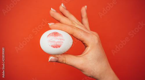 Leinwandbild Motiv Print of red lips on white egg. Red lip imprint on easter egg on red background. Lipstick kiss print.