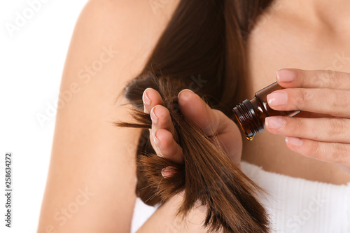 Leinwandbild Motiv Woman applying oil onto hair against white background, closeup