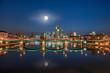 Leinwandbild Motiv Die Skyline von Frankfurt am Main am Abend mit Vollmond