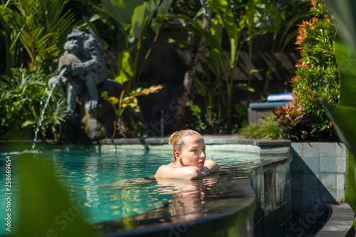 canvas print picture Sensual young woman relaxing in outdoor spa infinity swimming pool surrounded with lush tropical greenery of Ubud, Bali. Wellness, natural beauty and body care concept.