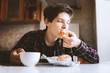 attractive man eat sandwich with cup of tea in hand