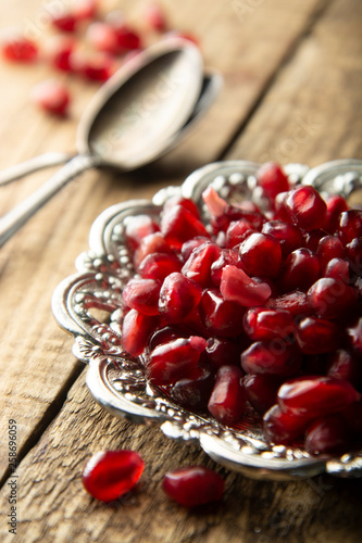Pomegranate seeds in vintage metal beautiful palte, over rustic wooden background. Ripe pomegranate closeup, healthy fruit ingredient. - 258696059