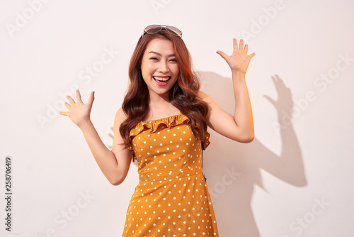Portrait of cheerful fashion girl going crazy in a orange polka dots dress isolated on beige