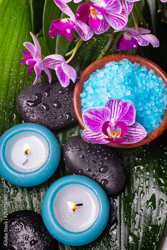 bowl with lavender-scented bath salt, orchid, massage stones, covered with water drops, and scented candles. - 258716485