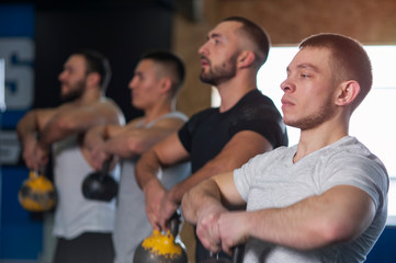 Male Focused Friends Lifting Kettlebells During Workout Session in Gym