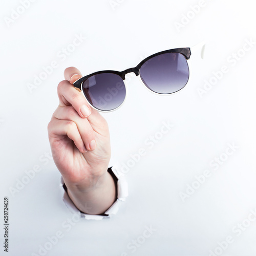 Leinwandbild Motiv Female hand out of the hole in the paperman, holding sunglasses for vision. Isolate on white background.