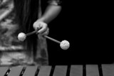 The hand of a girl playing a vibraphone in black and white