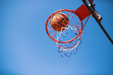 Basketball ball and hoop isolated on blue sky