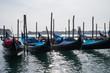 Many gondolas tied to long stumps in Venice