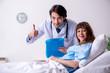 Leinwandbild Motiv Male doctor visiting female patient in ward