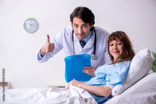 Leinwanddruck Bild Male doctor visiting female patient in ward