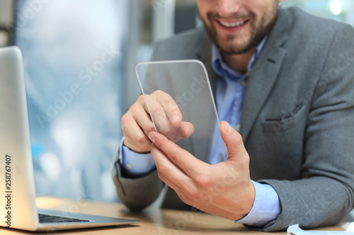 Future concept. Businessman holds futuristic transparent smart phone. © ty