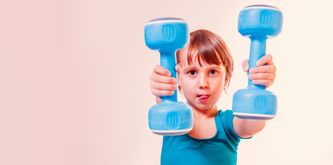 Fit little cute child girl in sportswear focused on lifting a dumbbell during an exercise class.  Sport lifestyle, health, power, success concept. © zwiebackesser
