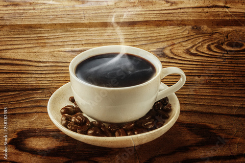 Hot coffee with hot steam and coffee beans on wooden table