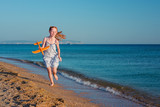 Happy red-haired child playing with an toy plane and running along the sandy beach of the sea against a blue sky and enjoying the rays of the summer sun and freedom.