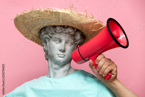 Antique bust of male in hat with red megaphone on pink background © Masson
