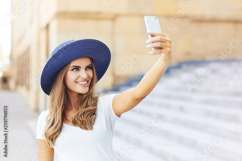 fototapeta na ścianę Young woman taking selfie while standing in the city
