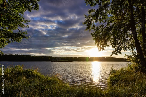 Summer Sunrise With Cloudy Sky Over Lake - 258797411