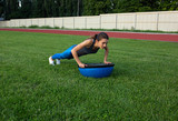 Fototapeta Fototapety sport - Slender woman doing excercises on the hemisphere at the stadium. Copy space © vpavlyuk