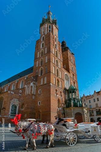 Horse carriage at Market square and St. Mary's Basilica in Krakow, Poland in summer sun light