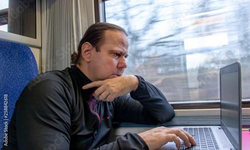Leinwandbild Motiv A adult man working on a computer on a train by the window. Passenger writes on laptop on a moving train.