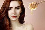 Young redhead woman and honey spoon prepare for facial mask.
