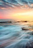 Incoming waves wash over rocks at sunrise