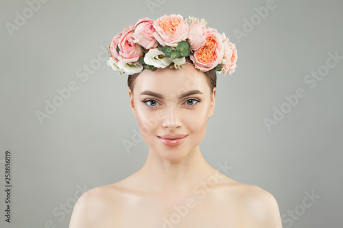 Pretty woman with healthy skin and rose flowers wreath portrait. Pretty candid girl with flowers. Facial treatment, skin care and cosmetology concept - 258886819