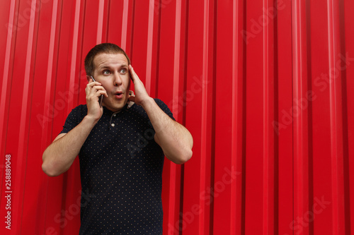 fototapeta na ścianę Shocked man using his cellphone on red background with free space. Image of young man standing over red wall background with mobile phone