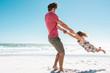 Leinwandbild Motiv Father playing with daughter at beach