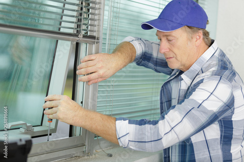 man installing a new blind on a window - 258898664