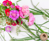Flower composition with a bouquet of pink peony flowers, cornflowers and red roses on a white background, top view flat lay