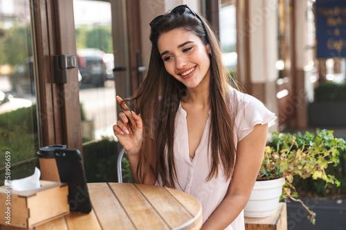 Leinwandbild Motiv Beautiful young woman sitting at the cafe table outdoors