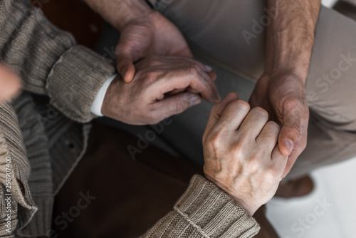 cropped view of retired father and son holding hands © LIGHTFIELD STUDIOS