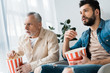 shocked senior father sitting with son and holding popcorn bucket while watching tv