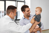 medicine, healthcare, pediatry and people concept - father with baby and doctor with stethoscope at medical office in hospital