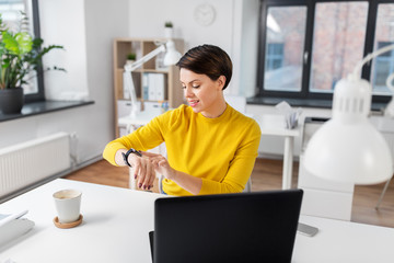 business, technology and time management concept - happy smiling businesswoman using smart watch at office
