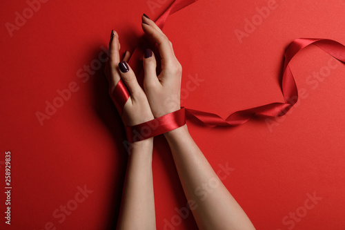 fototapeta na ścianę partial view of woman tied with satin ribbon on red background