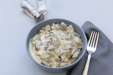 Curry mushrooms with creamy sauce on gray wooden background. Healthy eating or vegetarian concept. Copy space.