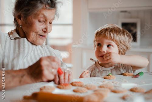 Leinwandbild Motiv A senior grandmother with small toddler boy making cakes at home.