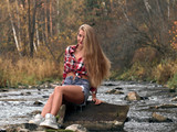Fototapeta Fototapety na ścianę - Slim athletic blonde in shorts and a plaid shirt sits in the middle of the river on the stone. © drouk