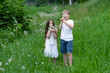 A boy with a girl playing in a field with dandelions.