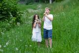 Fototapeta Fototapeta z dmuchawcami - A boy with a girl playing in a field with dandelions. © Sergey Kohl