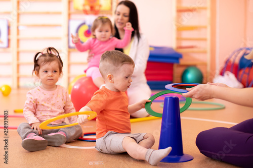 Nursery babies group doing sport in gym - 258939803