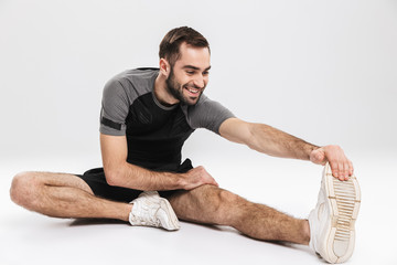 Sports fitness man isolate over white wall background make stretching exercises. © Drobot Dean