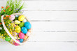 Leinwandbild Motiv Basket with easter eggs on rustic wooden table. Top view.