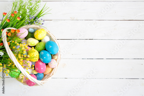 Basket with easter eggs on rustic wooden table. Top view. - 258963669