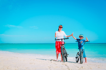 Happy mother and son biking at beach