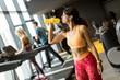 Leinwandbild Motiv Young women in yellow sport shirt are drinking water at the gym